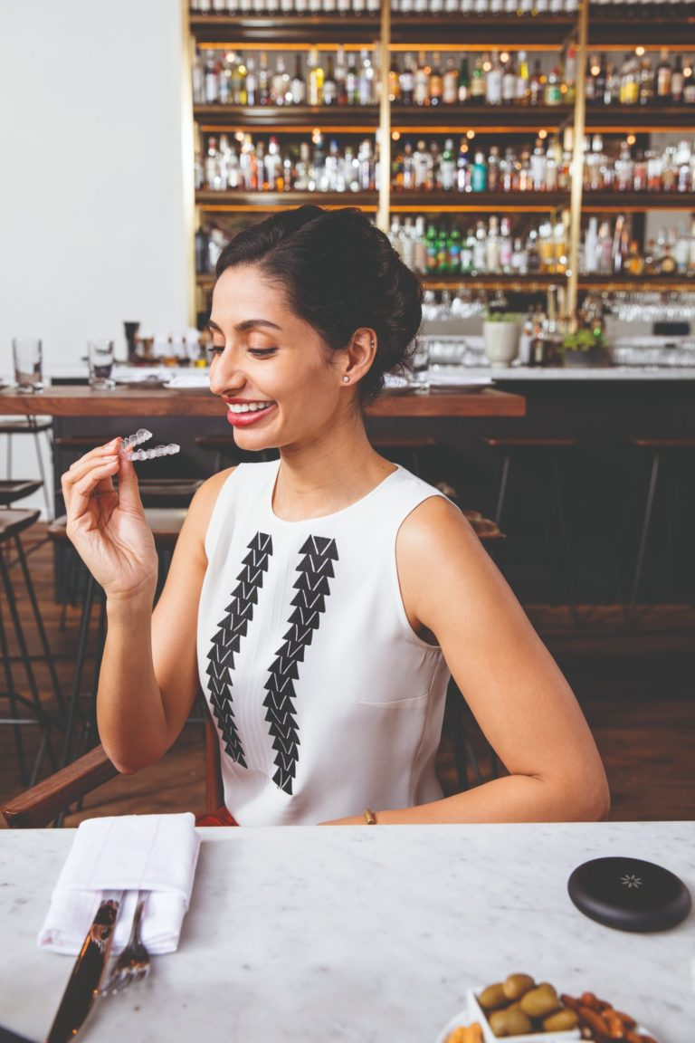 woman eating lunch with Invisalign aligners
