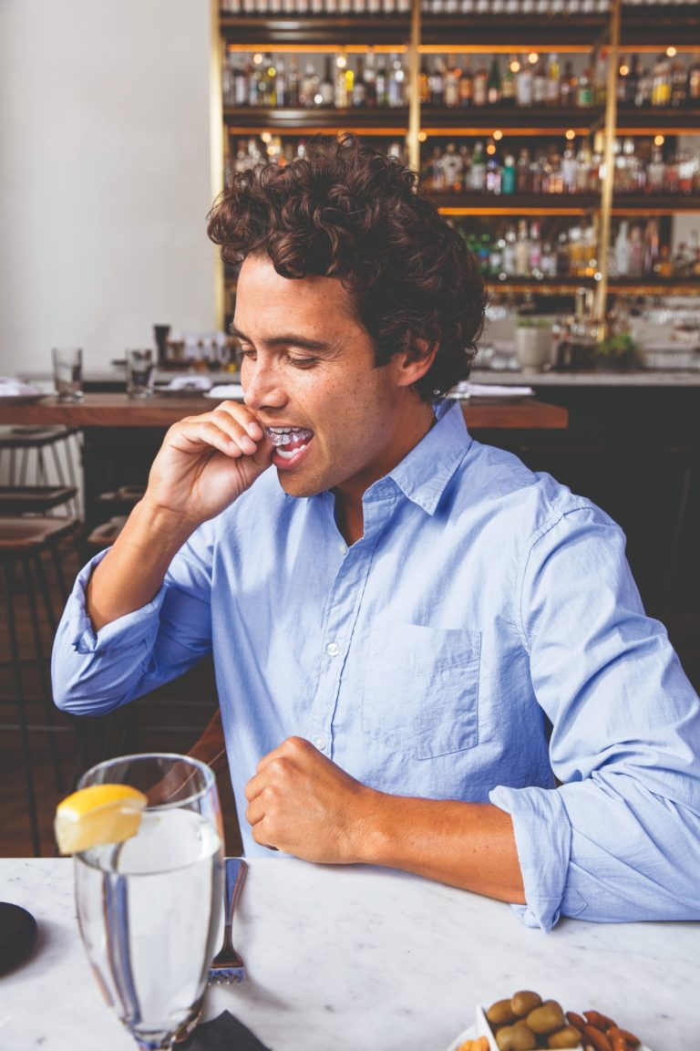 man eating lunch with Invisalign aligners