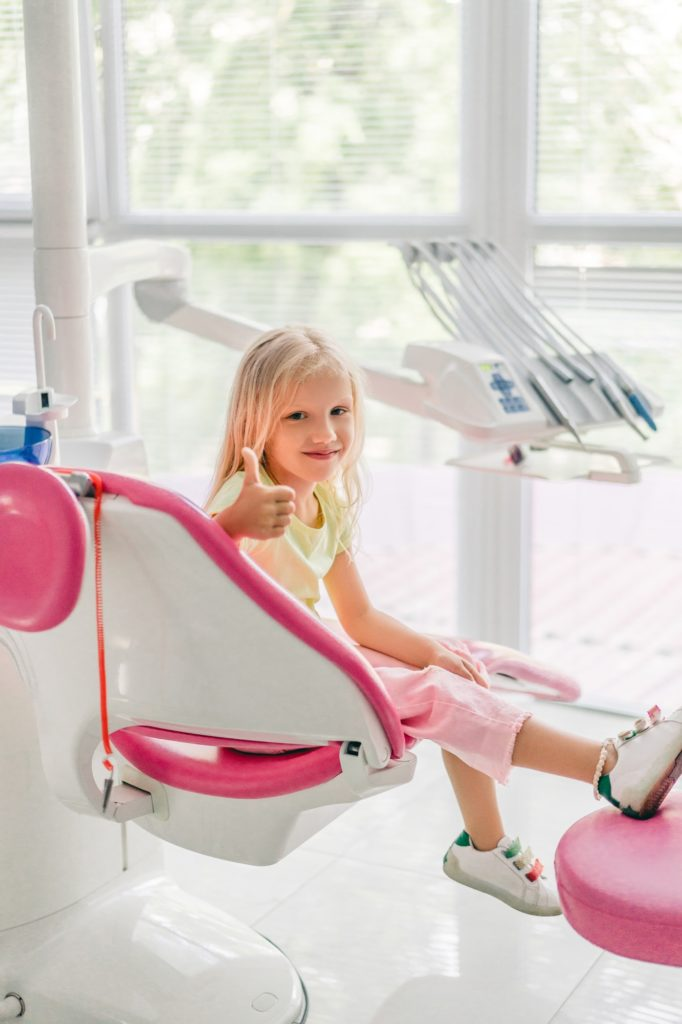 smiling kid showing thumb up while waiting for dentist at dentist office