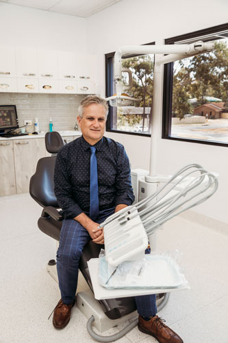 Dr Peter Wilkinson sitting in chair at Helensvale clinic