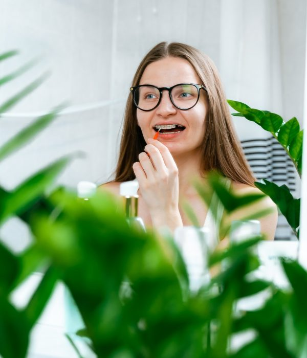 Young woman brushing her teeth in braces with orthodontic brush in bathroom looks in mirror. Hygiene
